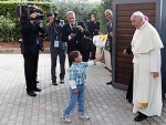 A child waves a flag as Pope Francis arrives at the Caritas residence in the Italian pilgrimage town of Assisi Oct. 4. The pontiff was making his first pilgrimage as pope to the birthplace of his papal namesake. (CNS photo/Stefano Rellandini, Reuters)