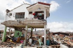 Survivors stay in their damaged house after Super Typhoon Haiyan battered Philippines
