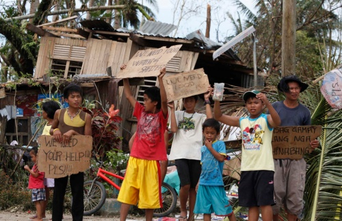 Young people hold signs asking for help and food after super typhoon hits Philippines