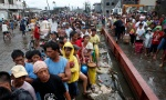 Typhoon victims wait in line for free rice at a businessman's warehouse after super typhoon hits Philippines