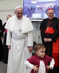 Child walks away after greeting Pope Francis as he visits Parish of San Cirillo Alessandrino in Rome