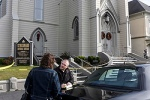 Investigator talks with woman outside church after pastor found slain inside rectory