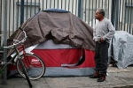 Man stands outside tent on Skid Row in downtown Los Angeles in 2013