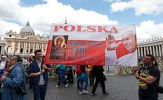 Pilgrims carry banner showing Our Lady of Czestochowa and St. John Paul II
