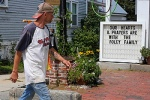 A man walks past a sign outside a shop Aug. 20 put up in memory of James Foley in his hometown of Rochester, N.H. Foley, a freelance war correspondent and a Marquette University alum, was killed at the hands of the Islamic State militant group. (CNS phot o/Brian Snyder, Reuters)