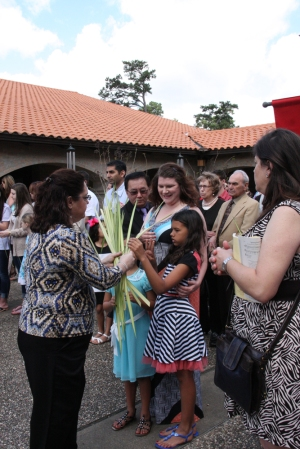 Valerie Brocato distributes palms to parishioners.