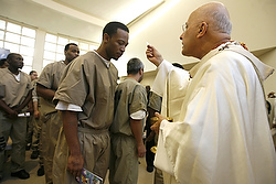 Cardinal Francis E. George of Chicago gives Communion to detainees during Mass at the Cook County Department of Corrections in Chicago on Christmas Day in 2008. Cardinal George, 78, died April 17 after a long battle with cancer. (CNS photo/Karen Callaway, Catholic New World) See GEORGE-REACT (UPDATED) April 17, 2015, and OBIT-GEORGE (SECOND UPDATE) April 20, 2015.