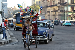 A man rides a bicycle taxi with several national flags on it along a street in late March in Havana. Pope Francis will visit Cuba in September before his trip to the United States. (CNS photo/Alejandro Ernesto, EPA)